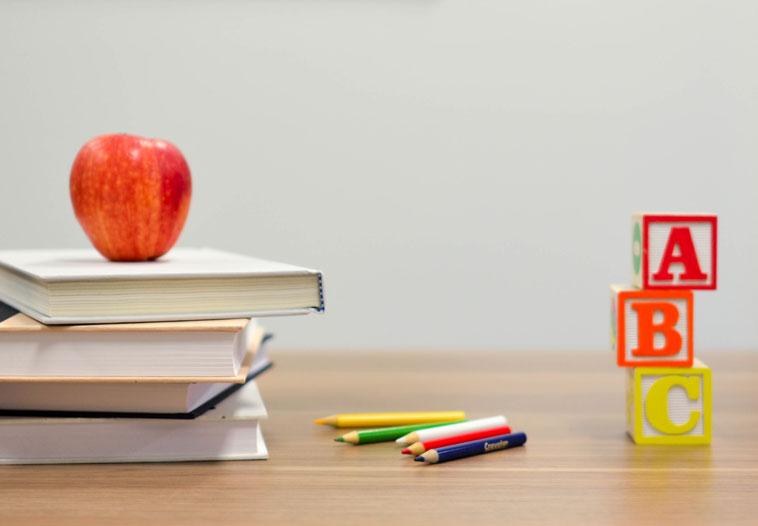 Tisch mit Büchern, Apfel, Stiften und Bauklötzen